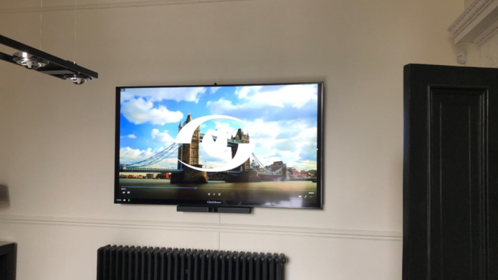 Customer's AV installation with System Video logo on screen imposed on a London Tower Bridge background picture. ClickShare and Bose VB1 videobar fitted underneath screen.