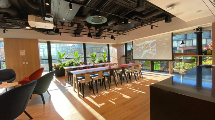 Collaboration space with ceiling speakers and projection screen.
